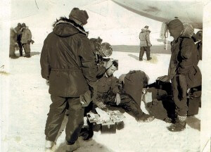 1956 McMurdo Sound – Capt. Cassity, injured during flight preparation/equipment loading, is rendered first aid by Flight Surgeon. Gen McCarty and Col. Crosswell look on.