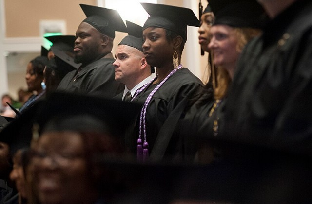 Erik Nemecek, center, stands with the rest of the Bachelor of Science in Nursing students as Brenau University President Ed Schrader confers their degree upon them.