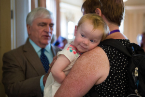 Emma Magness, 1, is held by her mother, Sarah Magness, WC '07, while she speaks with Brenau President Ed Schrader. (AJ Reynolds/Brenau University)