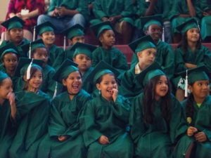 Students laugh while watching a video recapping their experiences during the commencement ceremony for the RISE Program on Friday, July 14, 2017 at Fair Street School. (AJ Reynolds/Brenau University)