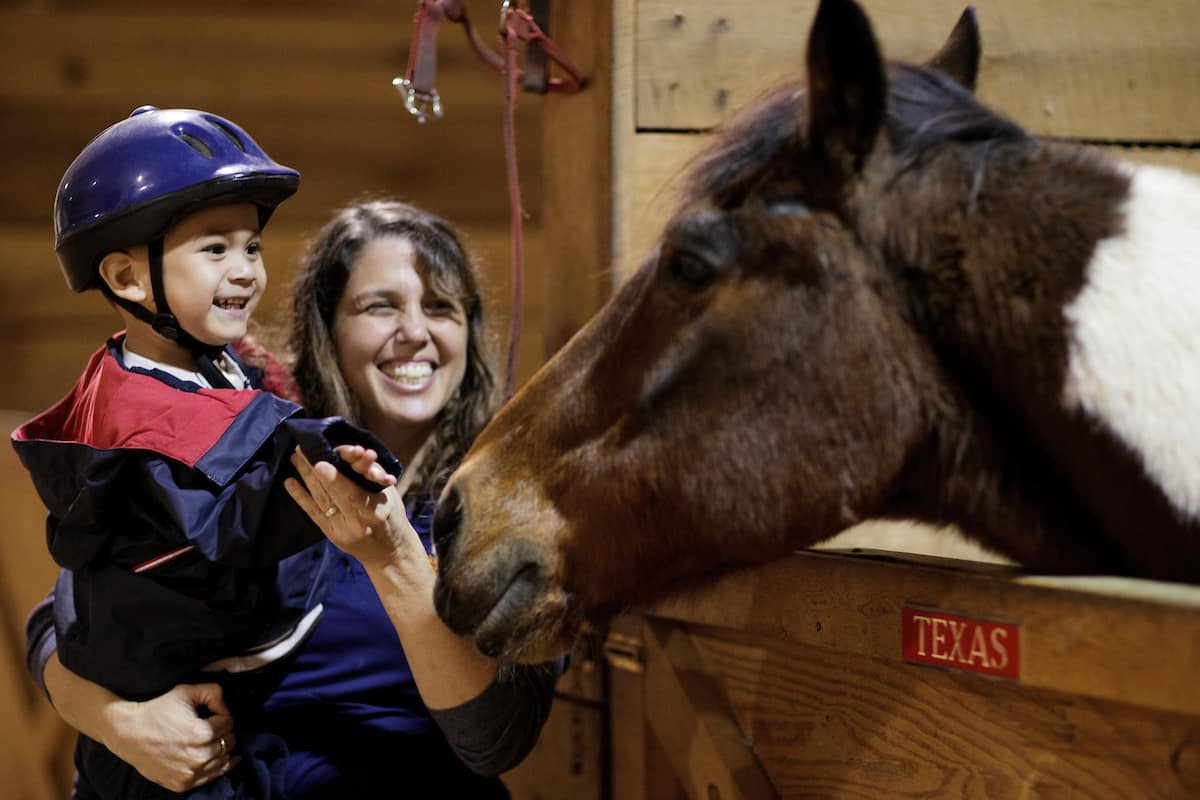 Nolina Varley, BU '01, an occupational therapist at Walker Therapy, helps a young boy greet a horse before an equine therapy session. (AJ Reynolds/Brenau University)