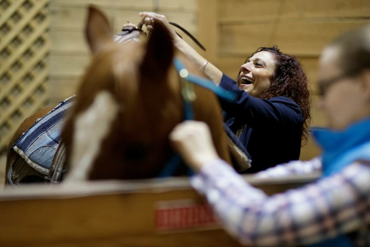 Nicole Walker, BU '01, owner and occupational therapist at Walker Therapy, saddles a horse before an equine therapy session. (AJ Reynolds/Brenau University)