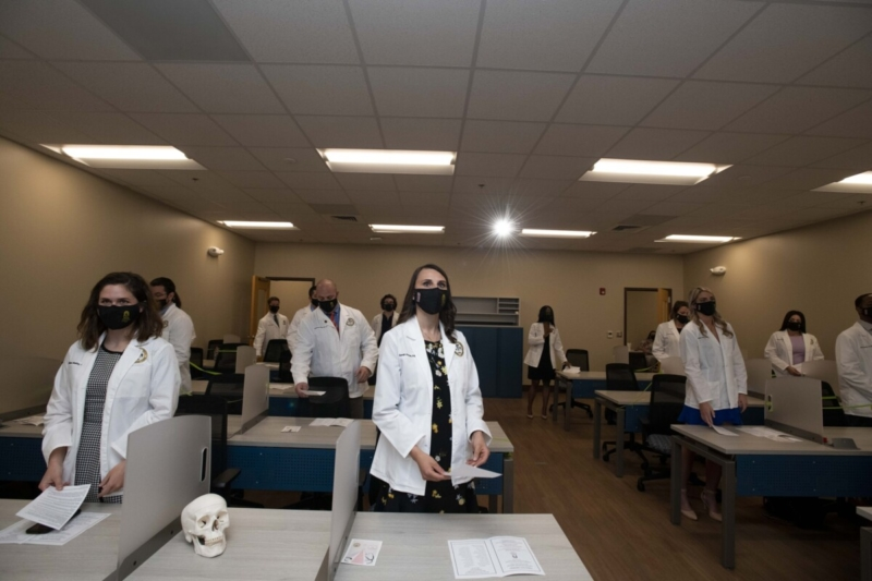 Students in white coats and masks stand in classrooms at their desks. A skull rests on a desk between two students.
